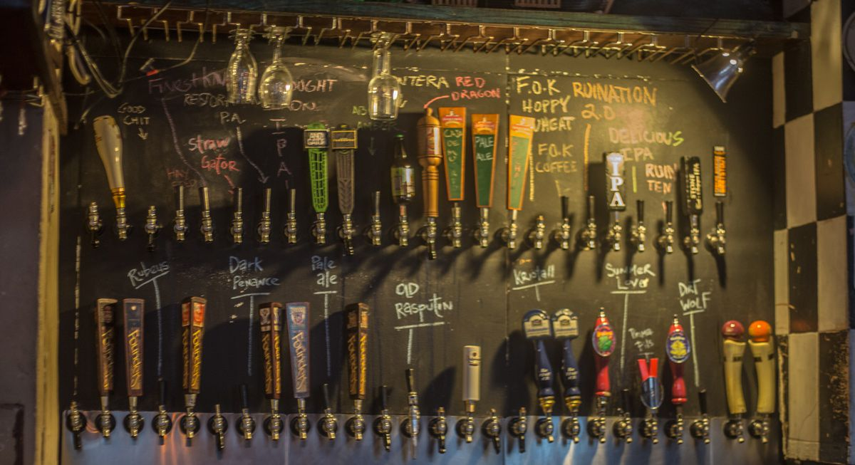 Two rows of taps on a blackboard with beers written in chalk