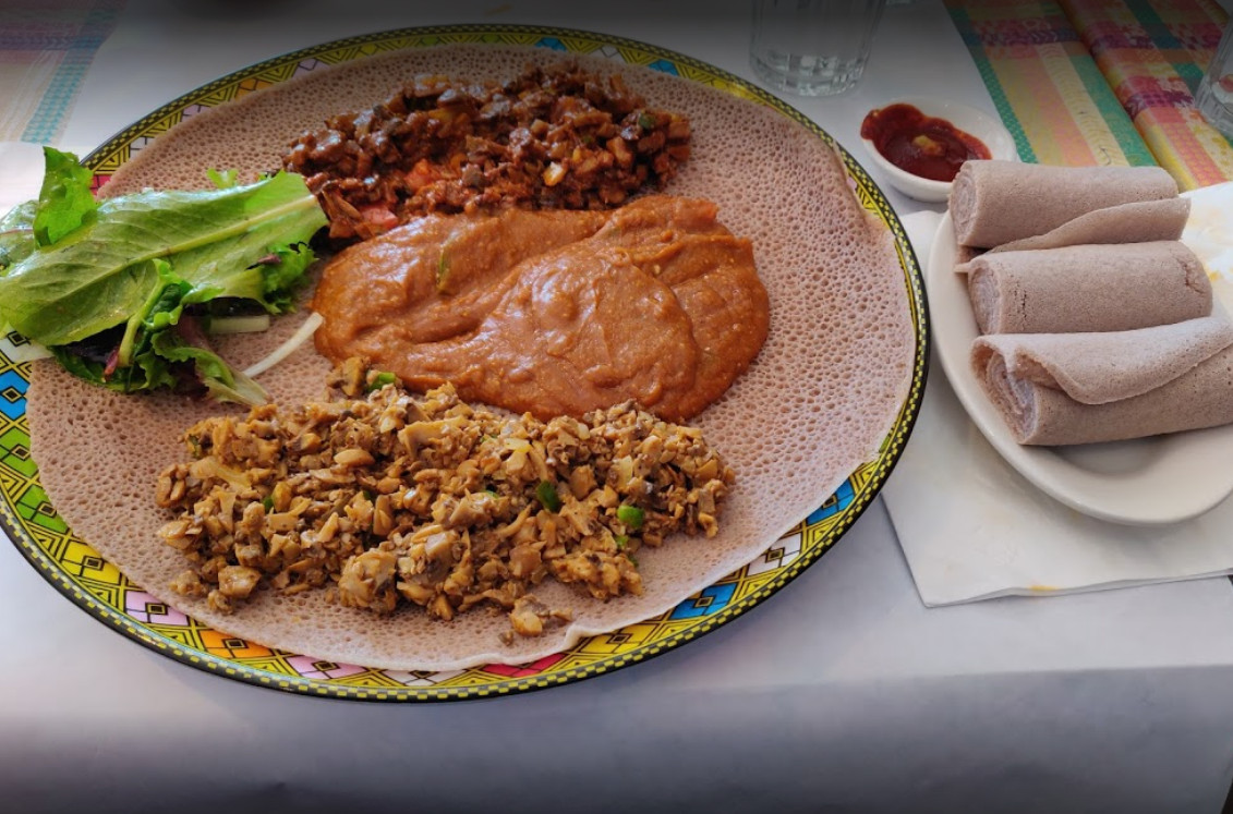 Three separate dishes placed atop injera bread