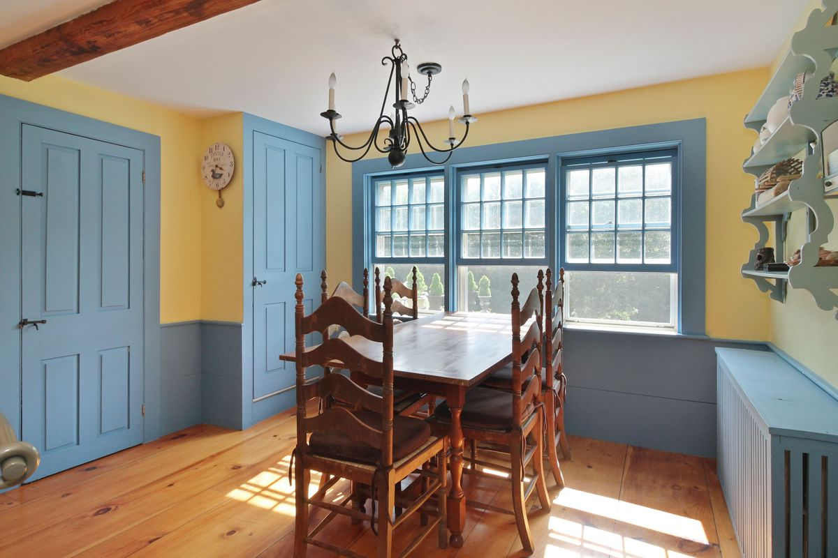A dining room features a wooden table with seating for six, wood floors, yellow walls, and light blue trim for the doors, windows, and wainscoting.