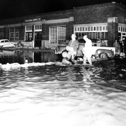 Salt Lake residences filling a gap in a sandbag wall In late April 1952. This scene is at about 950 South on Main Street in Salt Lake City.