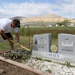 Curtis Larsen pulls weeds at his father's gravesite at the Bingham City Cemetery in Copperton on Thursday, May 25, 2017. The Jordan School Board has deeded the pioneer cemetery to Copperton Township after 44 years as owner and caretaker.