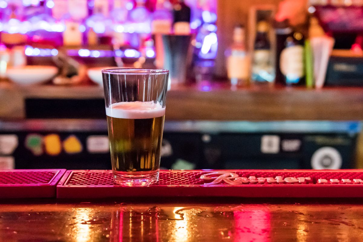 A half-filled glass of beer sits on top of a bar, with colorful neon lights in the background.