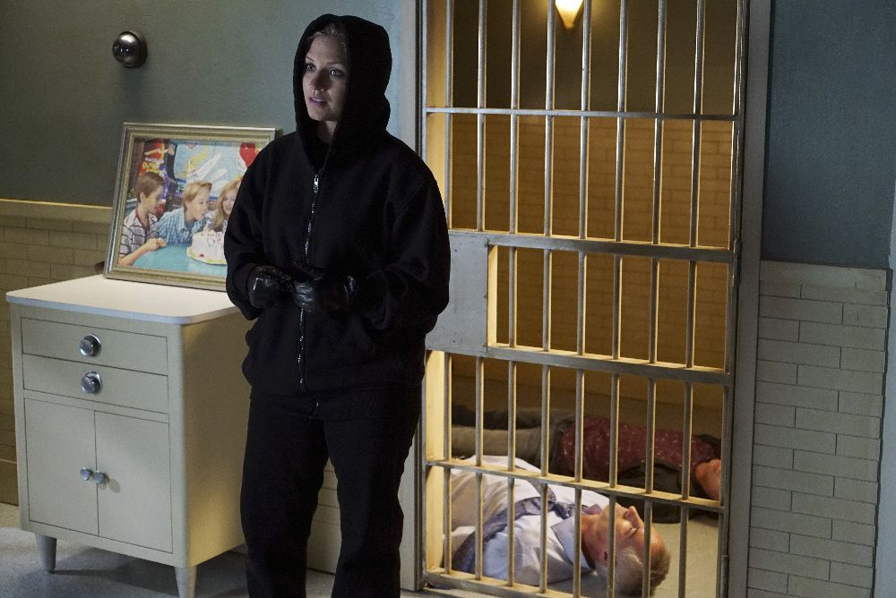 Charlotte in a room, in front of a painting of her and her siblings, with bars on the door, wearing a black hoodie, with her father and brother on the floor on the other side of the door.