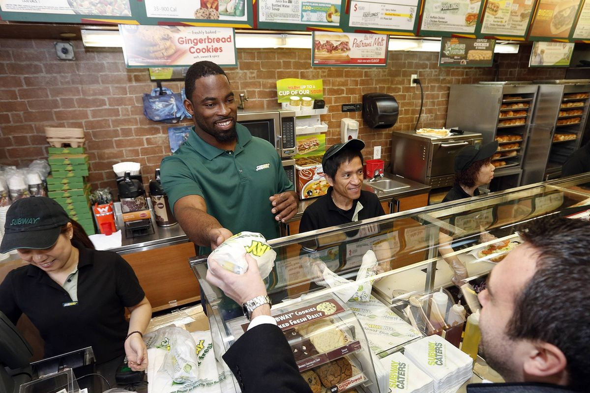 Justin Tuck works the counter at a New York City Subway on Tuesday