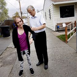 Ron Baker helps Mandi Shaw with her sweater at Shaw's home in Kearns on Wednesday, April 18, 2012.