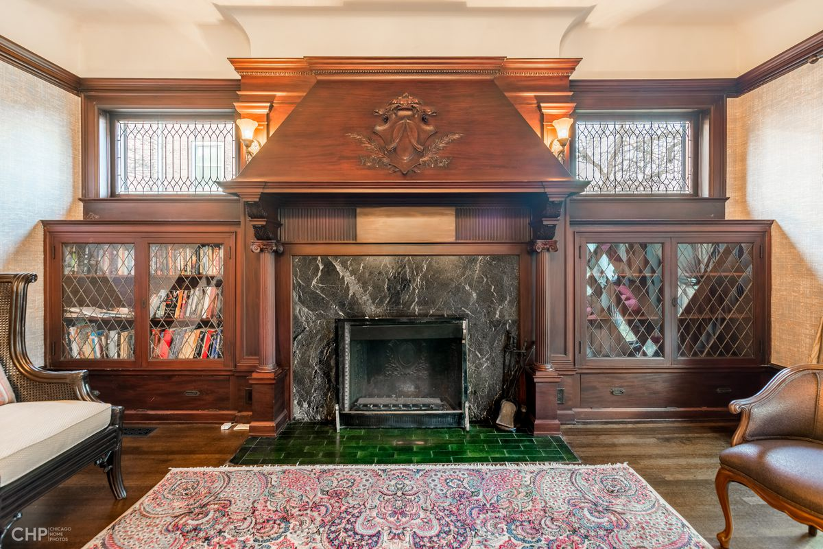 A wood fireplace with a stone surround and carved family crest on the hood.