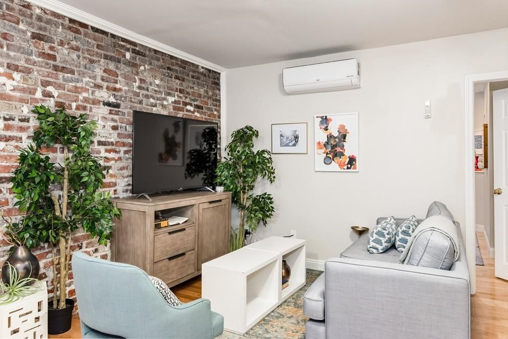 The corner of a small living room, with furniture facing a flat-screen TV.