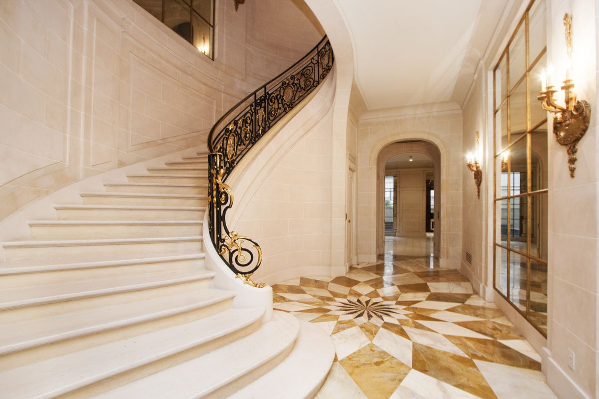 The entrance features a sweeping stone staircase and wrought iron railing with gold gilding.