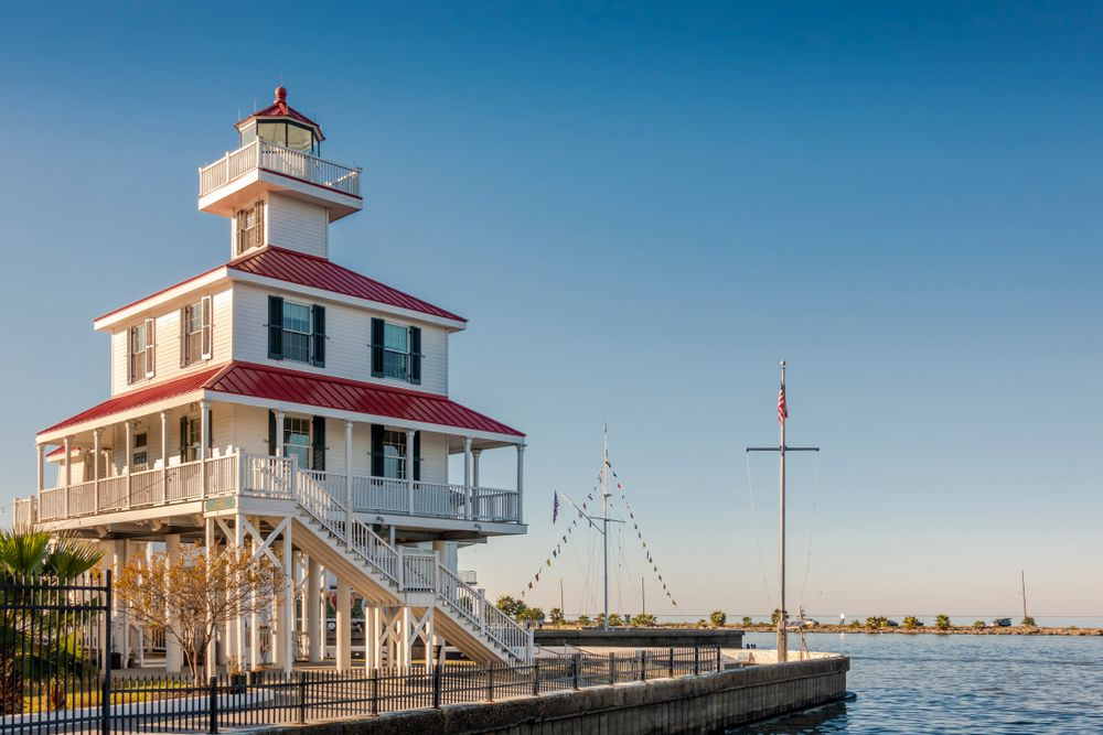 The exterior of the New Canal Lighthouse in New Orleans. The lighthouse is white with red decorative details. The lighthouse sits on a pier next to a body of water.