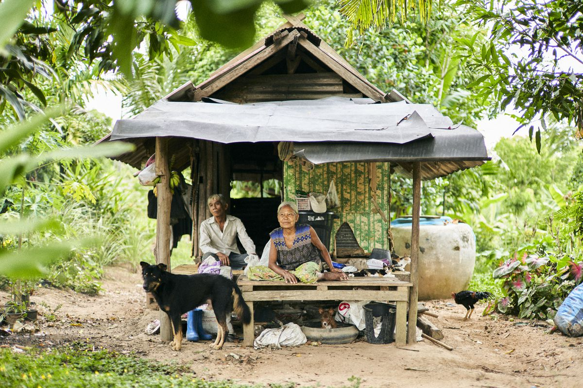 A couple sit inside of a wooden home with a dog