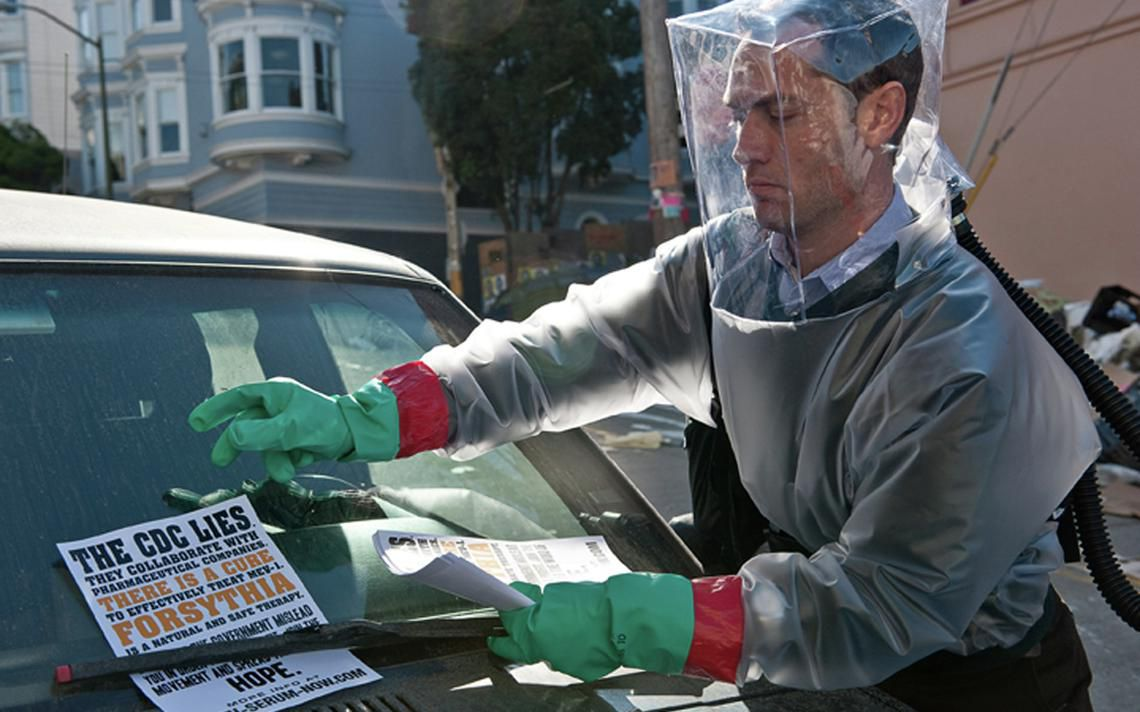 Jude Law, as conspiracy theorist Alan Krumwiede, in a protective suit sticking a flyer under a car windshield wiper in the movie Contagion.