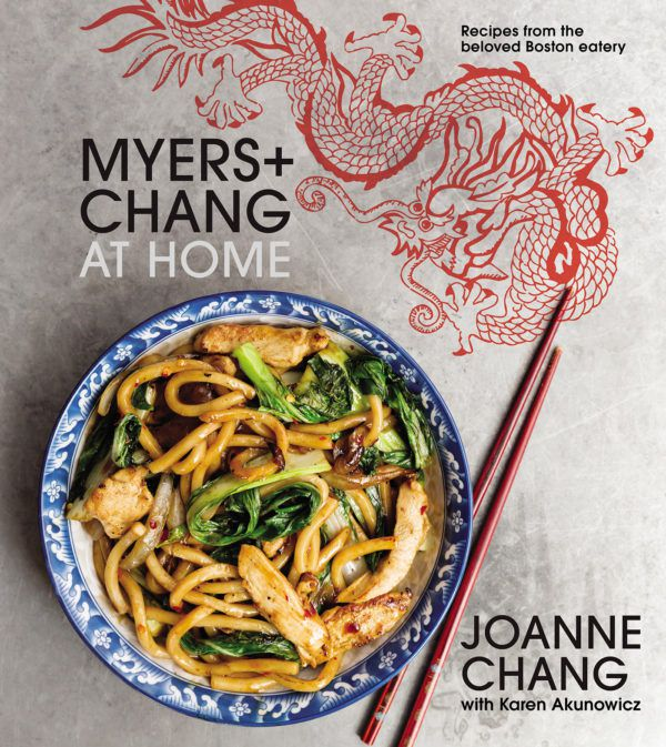 A cookbook cover features a bowl with a decorative blue rim. The bowl is full of a stir-fry with thick noodles; a pair of red chopsticks rests next to the bowl. A line drawing of a decorative red dragon is also on the cover.