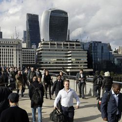 Commuters walk across London Bridge, with new security barriers, after work in London, Tuesday, June 6, 2017. British police on Tuesday named the third London Bridge attacker as an Italian national of Moroccan descent, and Italian officials said they had passed on their concerns about him to British intelligence officials last year.