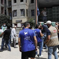 Members of the al-Ghina NGO distribute boxes of food for people in need, near the scene of last week's explosion, in Beirut, Lebanon, Tuesday, Aug. 11, 2020. In the absence of the state, acts of kindness and solidarity have been numerous and striking. Many extended a helping hand far beyond their circle of friends or family, taking to social media to spread the word that they have a room to host people free of charge. And on the streets, it was young volunteers with brooms, not government workers, who swept the streets littered with shattered glass.