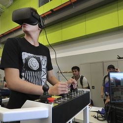 Blake Hession tries an equipment simulator as high school students look over Salt Lake Community College'sWestpointe Workforce Training & Education Center in Salt Lake City on Friday, Sept. 13, 2019.