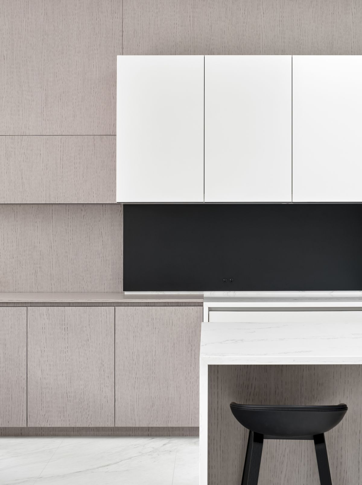 Kitchen with white island, black seats, and beige cabinets.
