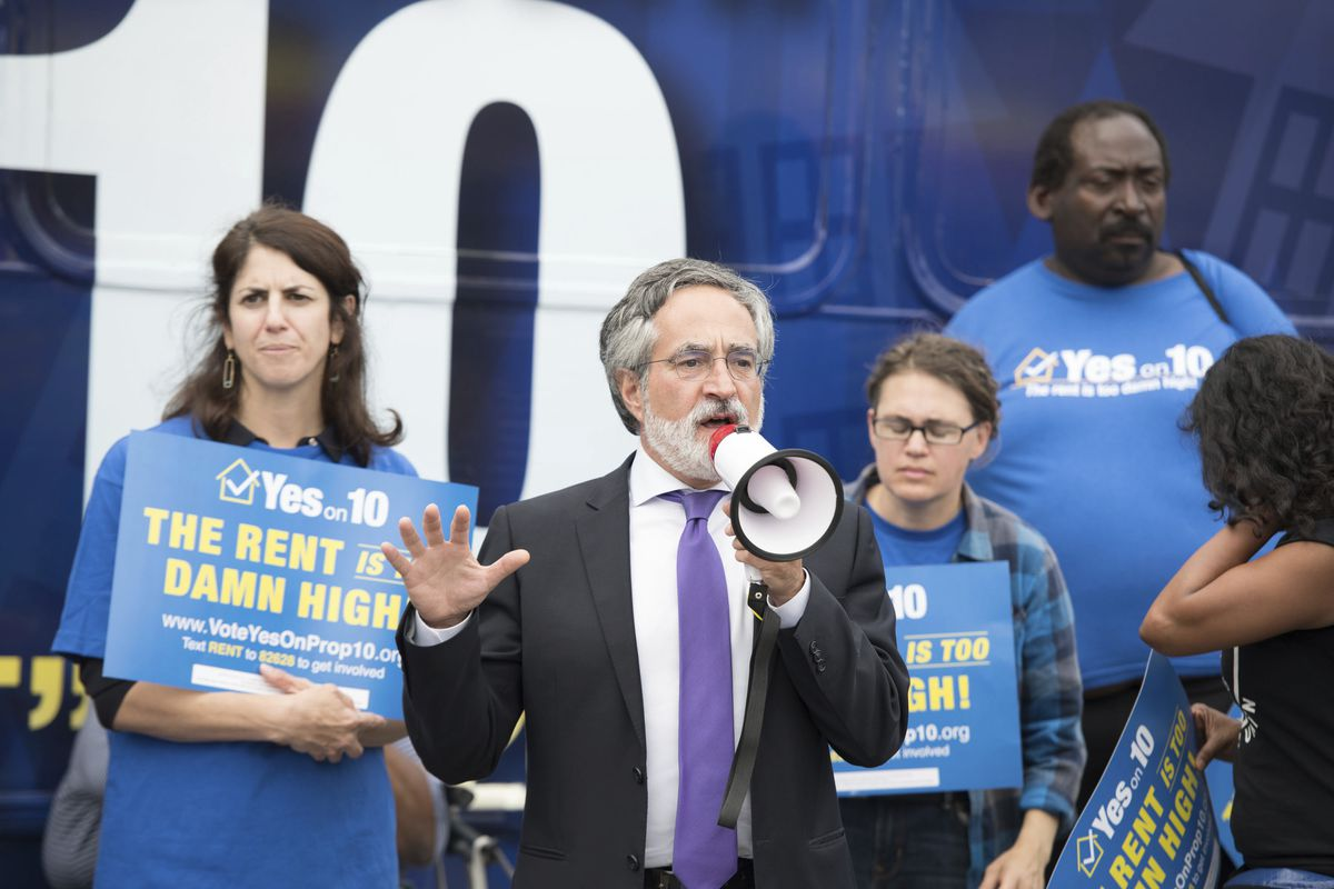 """San Francisco Supervisors Aaron Peskin addresses supporters during a Yes on 10 """"Rent Is Too Damn High"""" statewide bus tour in 2018."""