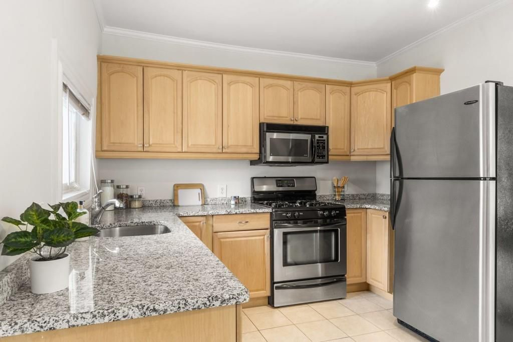 A kitchen with an L-shaped counter and a fridge.