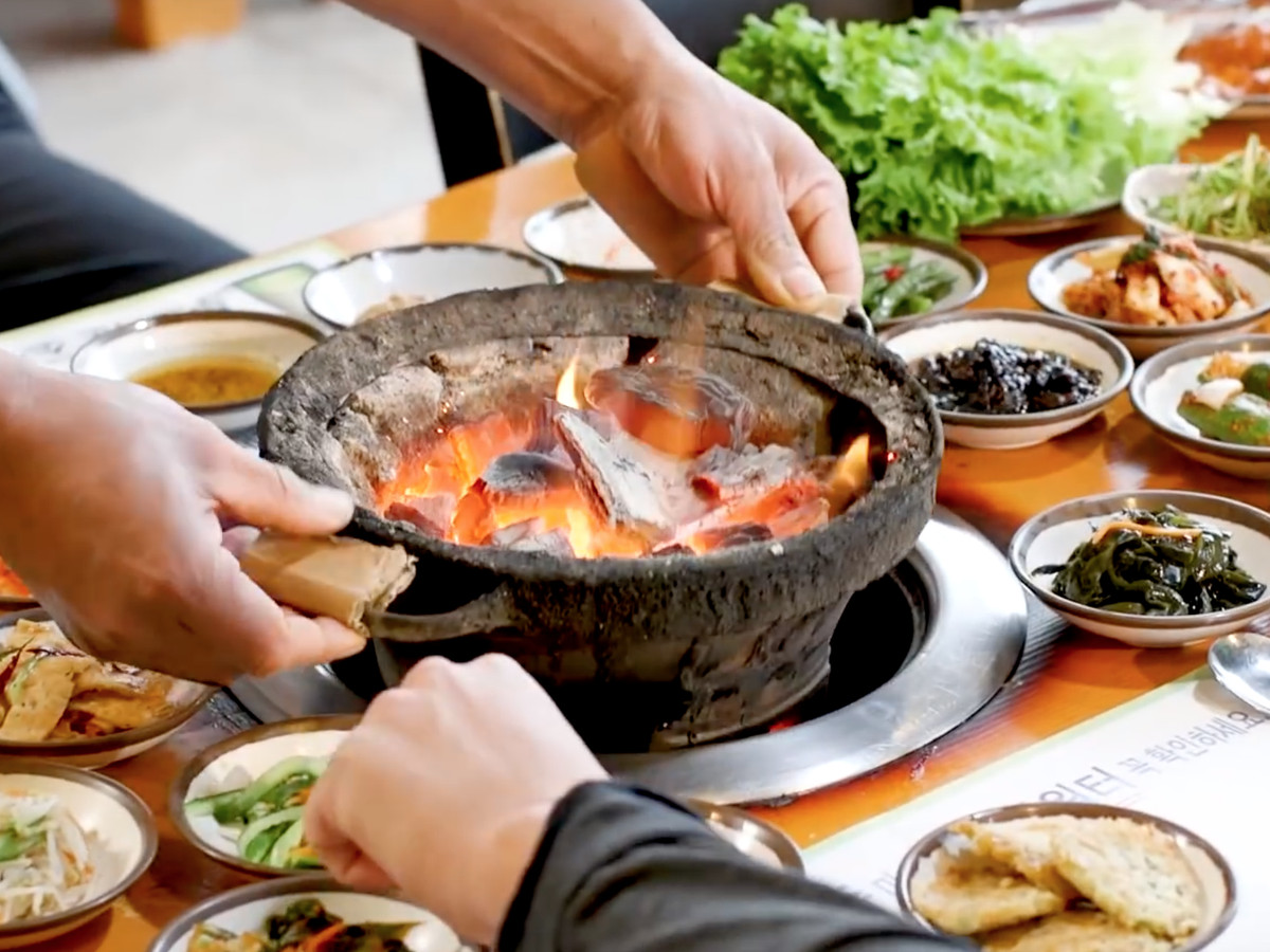 A cauldron of hot coals gets placed into the center of a grill table surrounded by Korean side items.