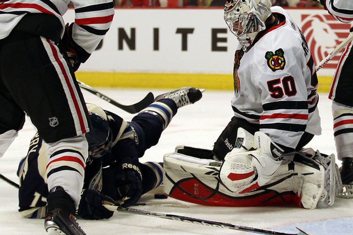 Corey Crawford of the Chicago Blackhawks stops a shot as Andrew Murray of the Columbus Blue Jackets falls to the ice at the United Center in Chicago Illinois. The Blue Jackets defeated the Blackhawks 4-3. (Photo by Jonathan Daniel/Getty Images)