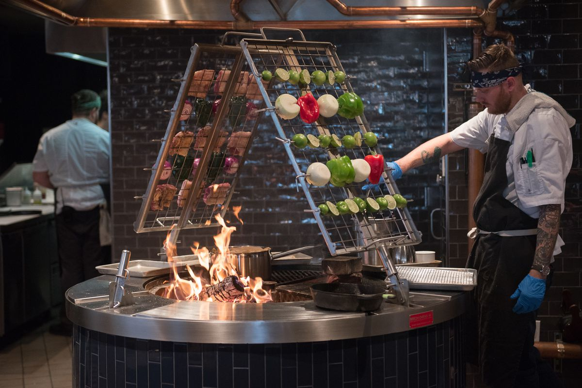A giant metal rack of vegetables roasting over a fire, with two chefs on either side.