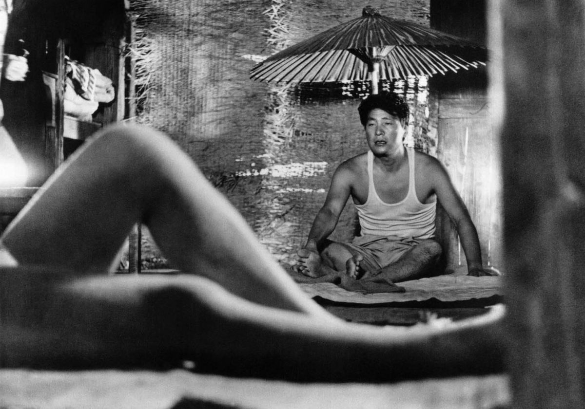 Niki Junpei (Eiji Okada) stares at a naked woman off-screen in Woman in the Dunes
