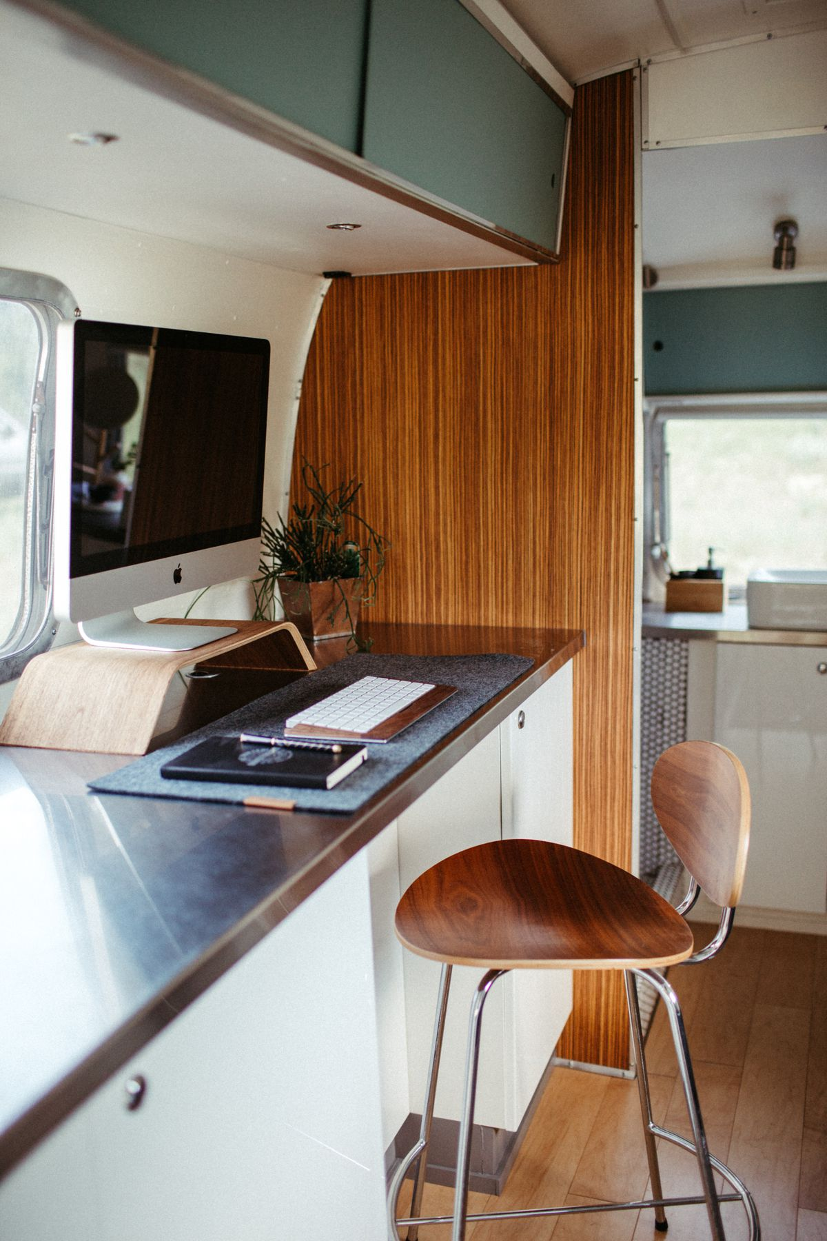 A work area inside the trailer has a wooden stool, computer, and stainless steel counters.