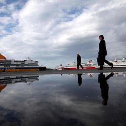 Reflected in water, a woman walks past at Piraeus port near Athens during a 48-hours strike at the port of Piraeus, near Athens, on Tuesday, April 10, 2012. Ferry services to Greek islands have been halted by a 48-hour strike that is expected to hit the start of the country's tourism season and celebrations for Orthodox Easter this Sunday.