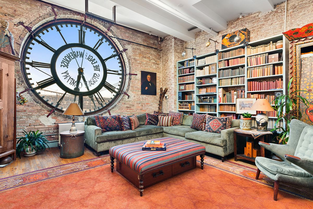 A living area with exposed brick, a large clock with views of the Brooklyn Bridge, a green couch, blue bookshelves, and beamed ceilings.