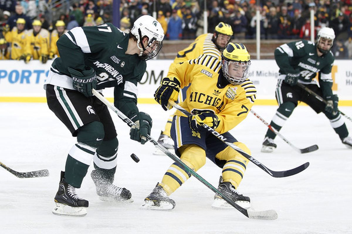 ANN ARBOR MI - DECEMBER 11:  Derek Grant #27 of the Michigan State Spartans battles for the puck with Chad Langlais #7 of the Michigan Wolverines at Michigan Stadium on December 11 2010 in Ann Arbor Michigan.  (Photo by Gregory Shamus/Getty Images)