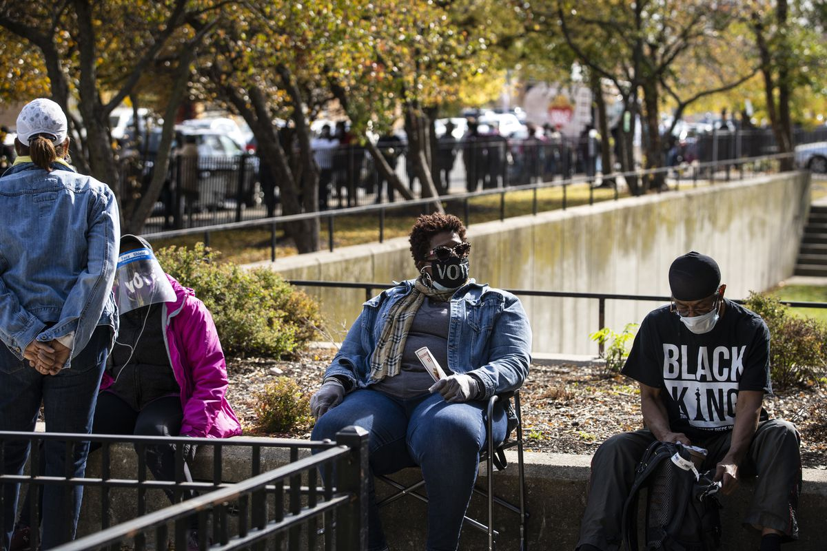 Melvina Lee, center, 56, of Bronzeville, waits in line for more than three hours to early vote in the General Election at the Dr. Martin Luther King Center Service Center in the Bronzeville neighborhood last month.