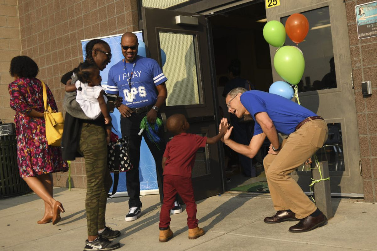 Denver Superintendent Tom Boasberg, right, high-fives students, parents, and staff on the first day of school at Escalante-Biggs Academy in August.