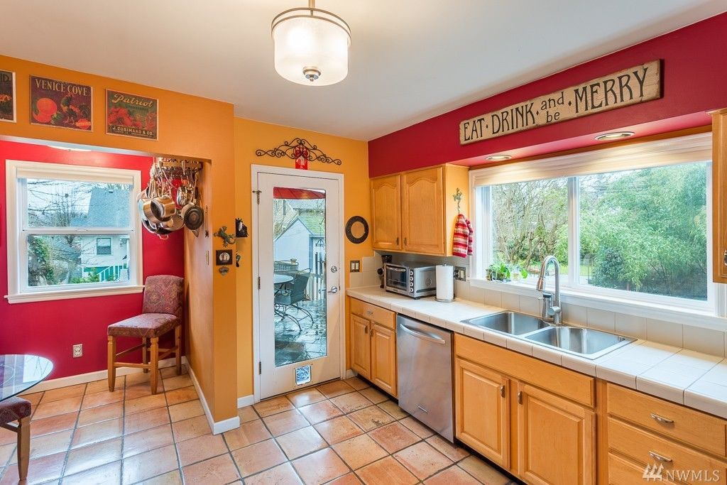 A kitchen features goldenrod and red walls and a breakfast nook.