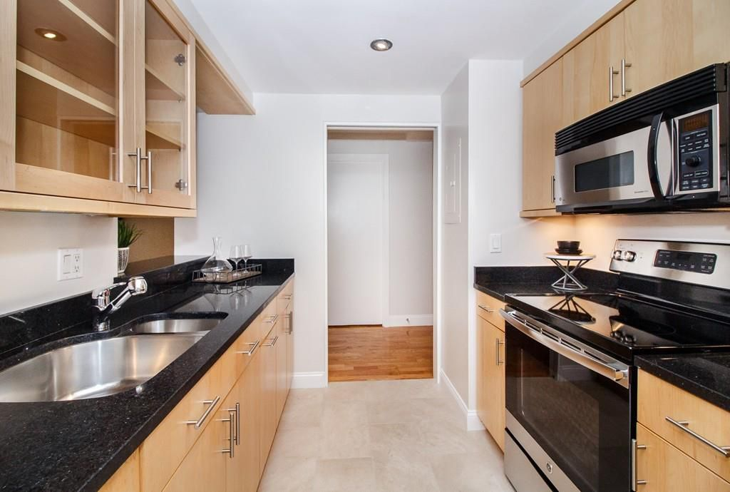 A long, narrow kitchen with counters and cabinetry on either side.