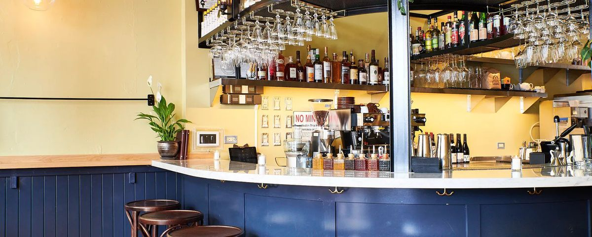 A picture of a circular bar with cocktail glasses and a coffee machine at Canard