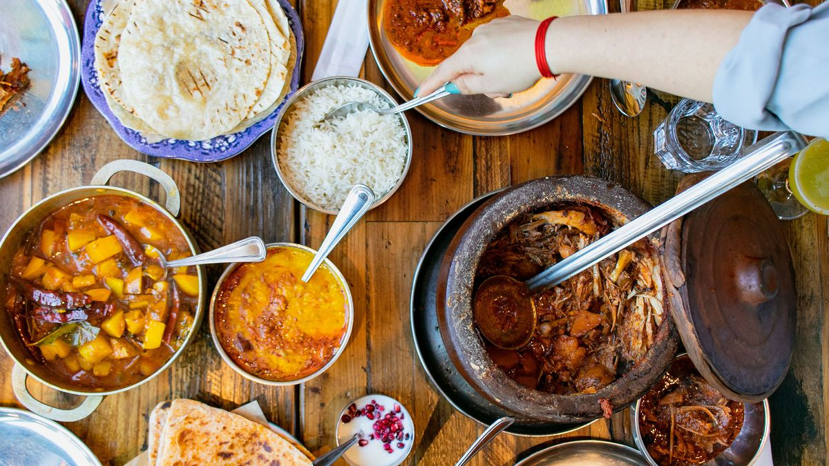 A spread of plates, bowls, and metal dishes of Indian food.