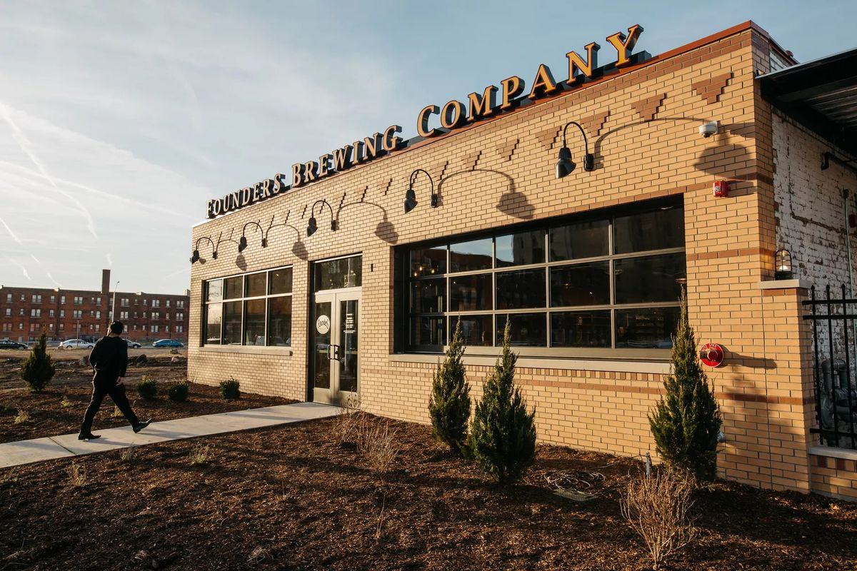"""Exterior of a brick building with long glass windows and """"Founders Brewing Company"""" in big letters on top."""