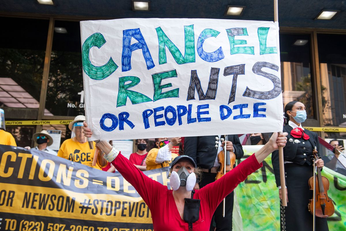 """A protester holds up a sign that reads, """"Cancel rents of people die."""""""