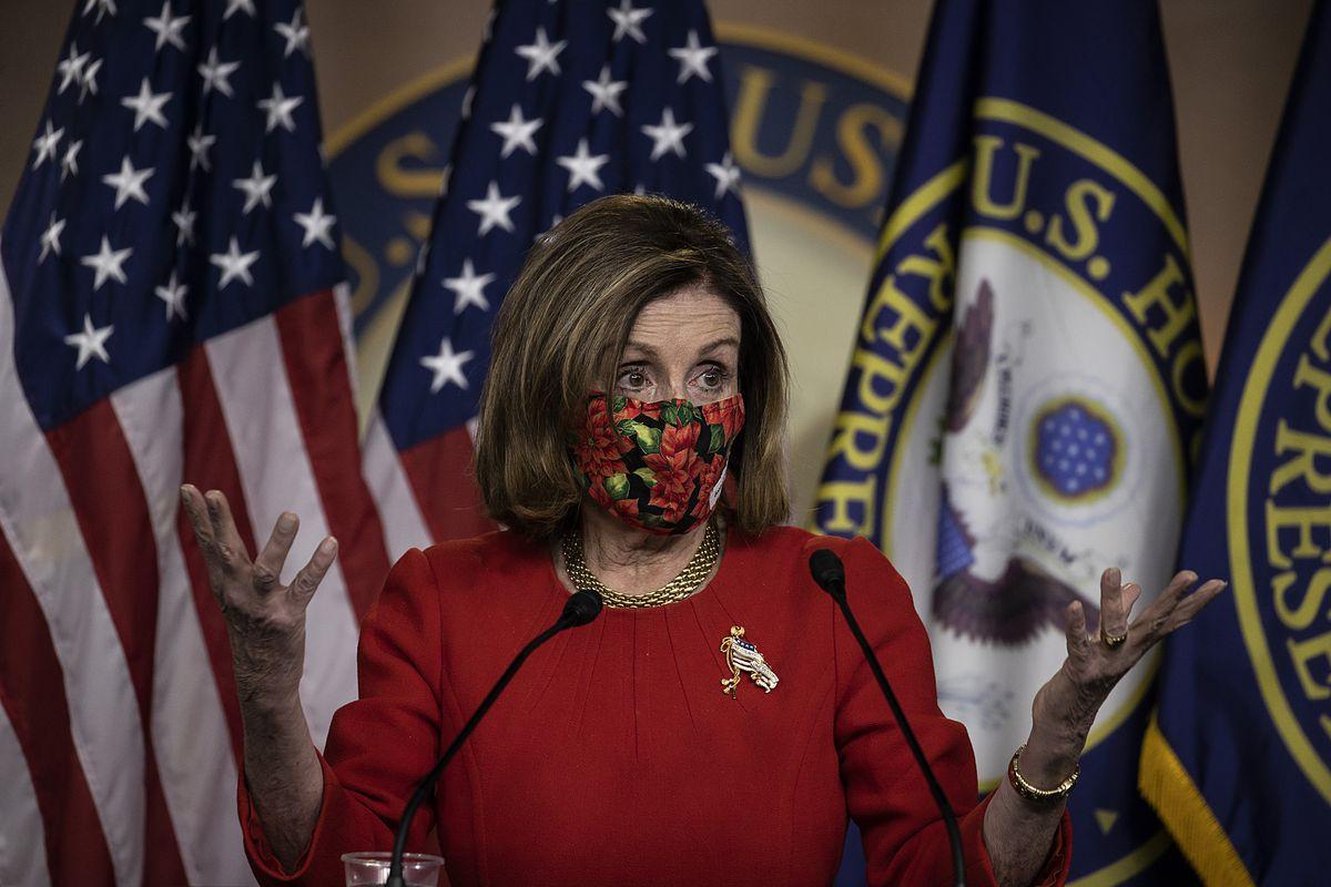 Nancy Pelosi at the podium wearing a mask.