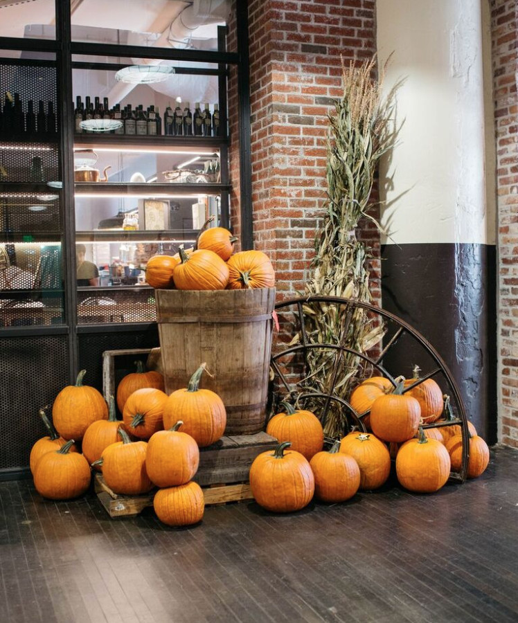 Pumpkins stacked on the floor and atop a barrel.