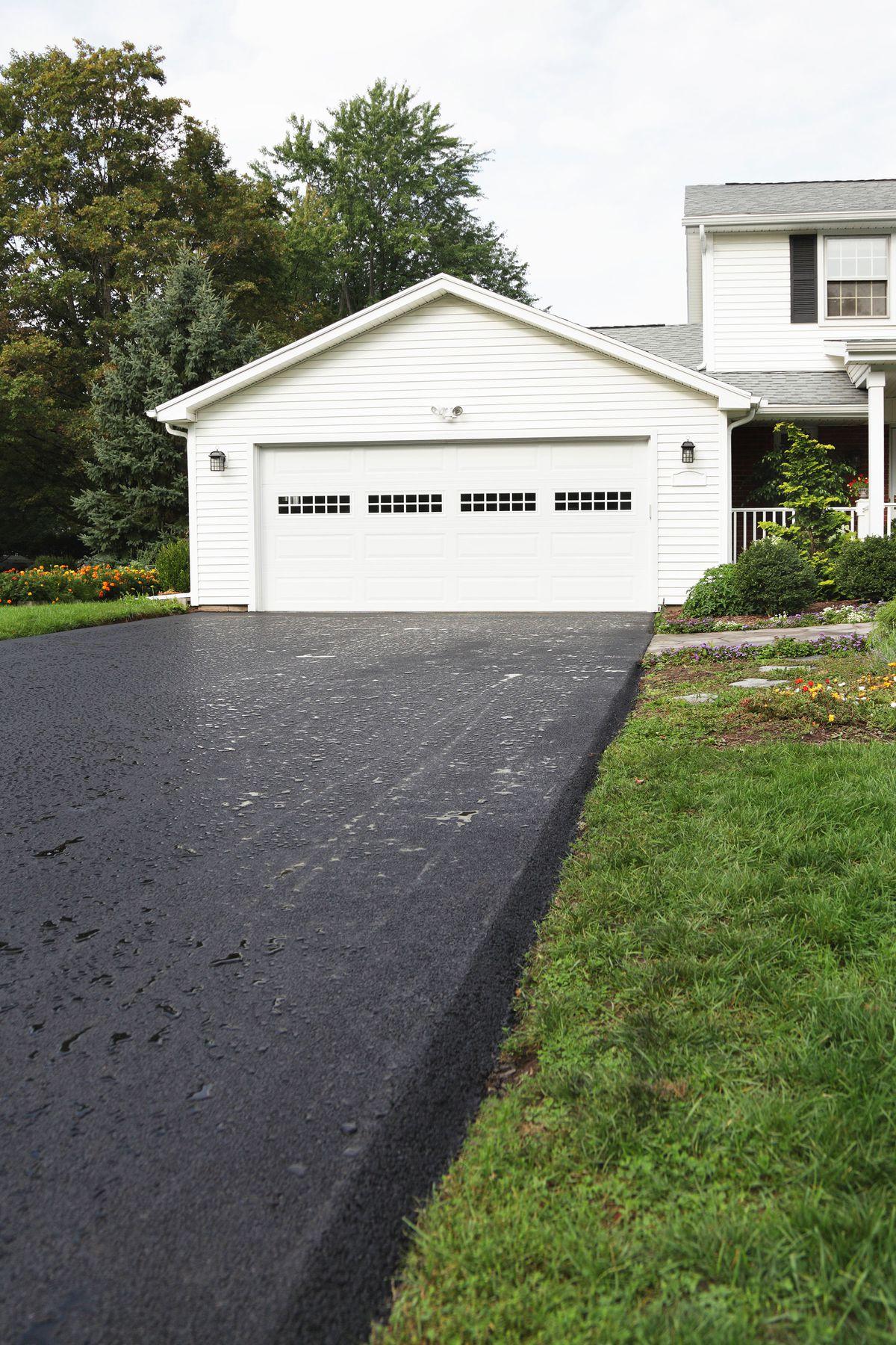 A newly installed asphalt driveway, wet with rain.