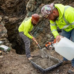 Bart Walker, left, and Landon Duckworth, of Strong Solutions, mix concrete as they work to close a mine tunnel opening above Layton on Wednesday, Nov. 18, 2020. Strong Solutions was contracted by the Utah Division of Oil, Gas and Mining to close the opening.