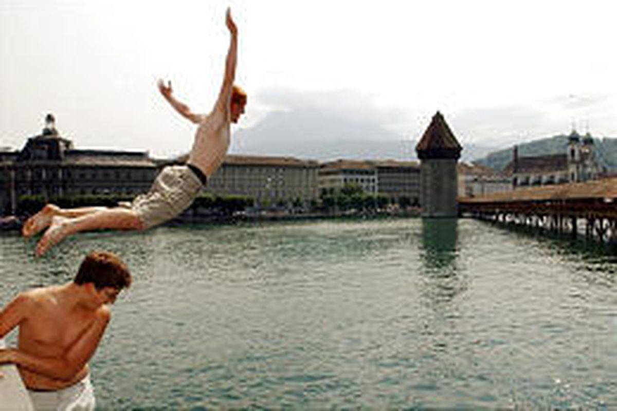 Two men jump into the river Reuss near the Chapel Bridge in Lucerne, Switzerland. Lucerne attracts many tourists.