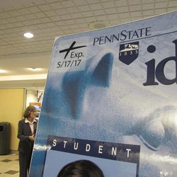 A display of a sample of a new Penn State ID card, now including an expiration date in the upper left-hand corner to comply with the Pennsylvania's new voter ID law, as seen at the school's Hetzel Union Building in State College, Pa., Wednesday, Sept. 26, 2012. Standing in the background is Secretary of Commonwealth Carol Aichele, whose department is responsible for implementing the tough new guidelines even while the law is under scrutiny in court.