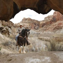 """Former Utah Jazz center Mark Eaton  rides his Clydesdale/Thoroughbred horse """"Big Tim"""" while riding horses down the Little Grand Canyon of the San Rafael Swell  Saturday, April 2, 2011, in the San Rafael Swell in Central Utah."""