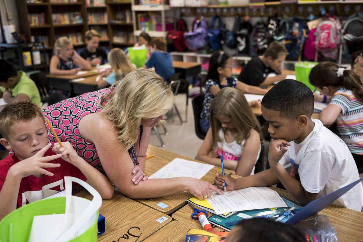 Fourth-grade teacher Stephanie Rice works with her students at Crosswind Elementary School in Collierville.