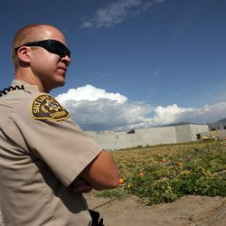 Officer Braxton Berrett watches over Salt Lake County jail inmates as they work in the inmate garden outside the jail in South Salt Lake on Wednesday, Sept. 14, 2011.