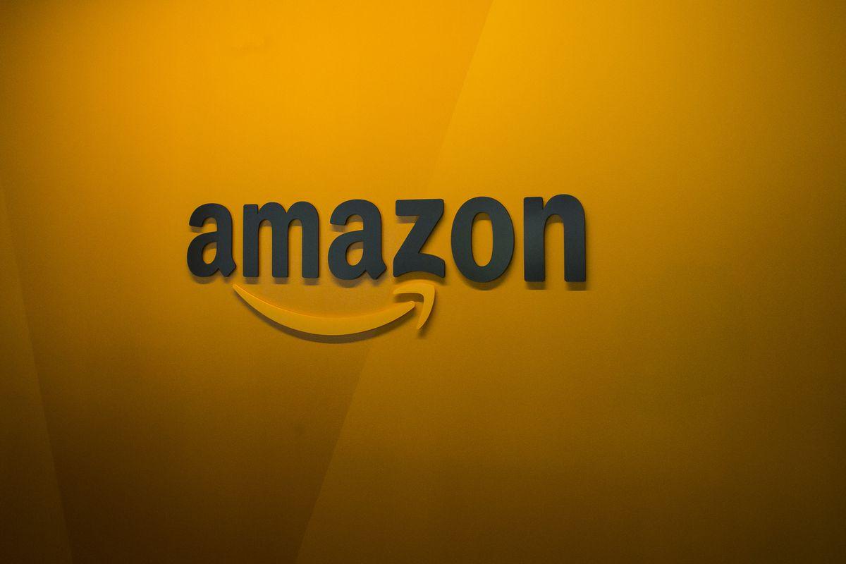 The Amazon logo hangs on a yellow wall.