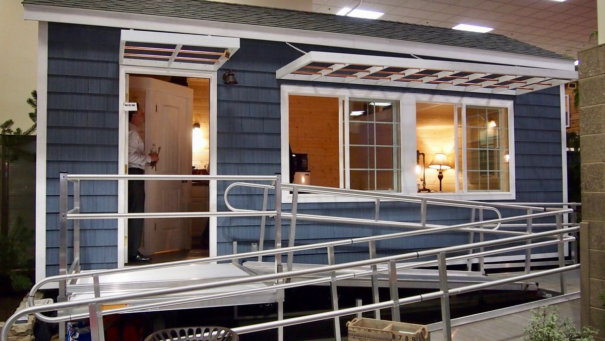 A small, blue tiny home with a ramp leading up