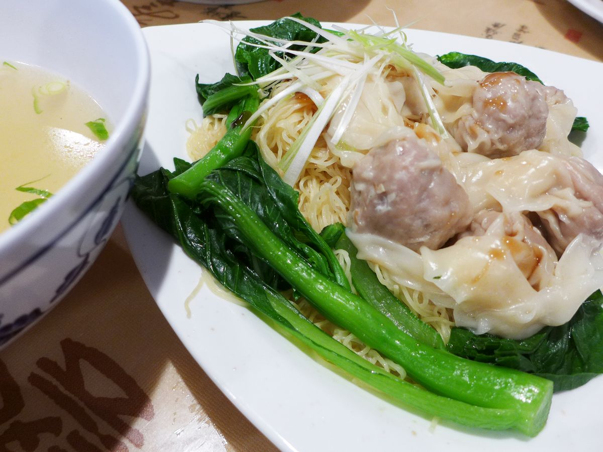 Wontons rest on a nest of noodles framed by bok choy, with soup on the side.